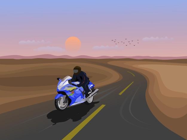 Man rijdt op een grote fiets op een snelweg met bergen en zonsondergang op de achtergrond.
