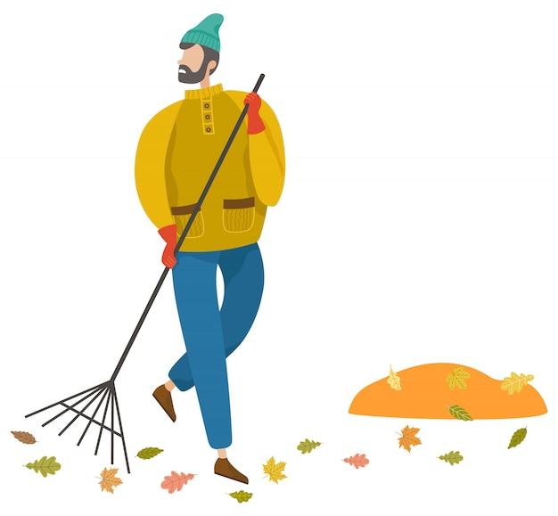 Man vegen gebladerte door bezem, herfstweer