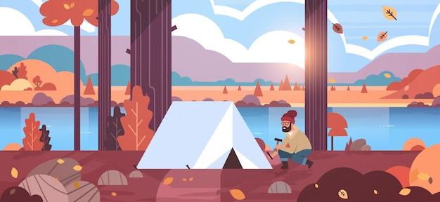 Man wandelaar camper installeren tent voorbereiden camping wandelen concept zonsopgang herfst landschap natuur rivier bergen