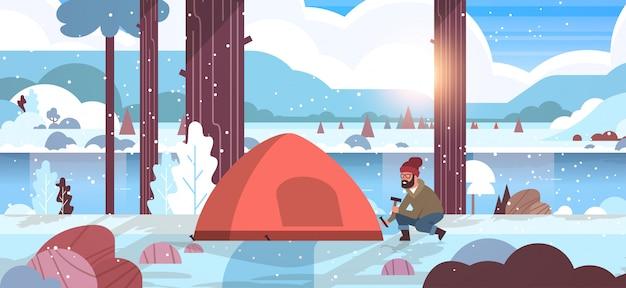Man wandelaar camper installeren tent voorbereiden camping wandelen concept zonsopgang winter sneeuwval landschap natuur rivier bergen