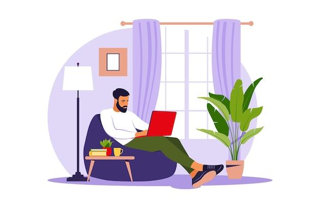 Man zit met laptop op zitzak stoel