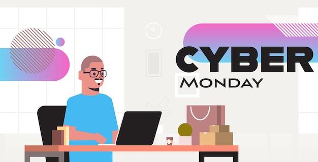 Man zit op de werkplek met behulp van laptop cyber maandag grote verkoop speciale aanbieding