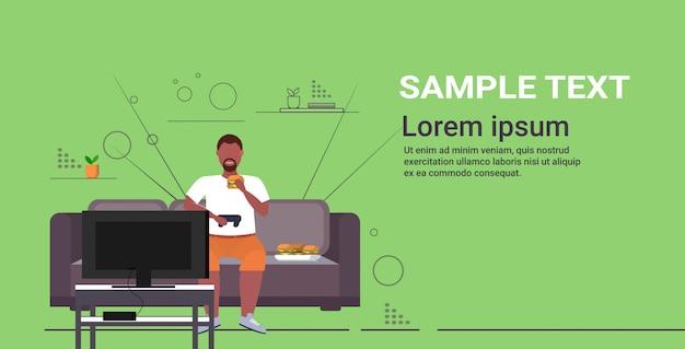 Man zittend op de bank eten hamburger met joystick gamepad overgewicht man spelen videospellen op tv zwaarlijvigheid ongezonde levensstijl concept horizontale volledige lengte