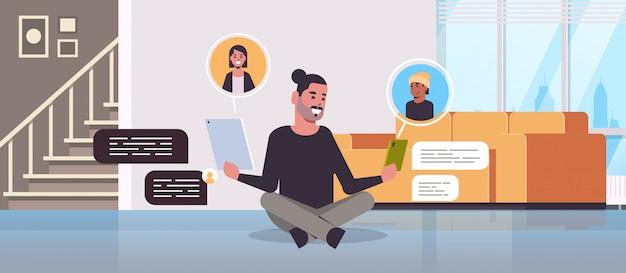 Man zittend op de vloer met behulp van chatten apps op digitale apparaten sociaal netwerk praatjebel communicatieconcept