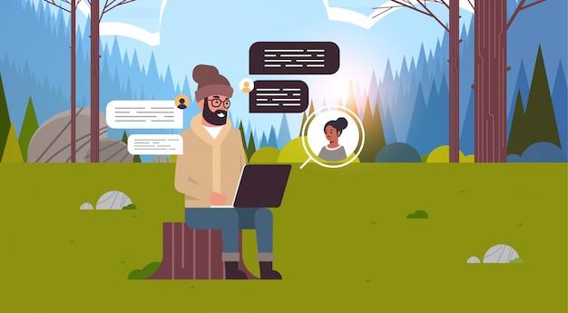 Man zittend op stomp in het bos met behulp van laptop man chatten met vrouw sociaal netwerk chat bubble communicatieconcept