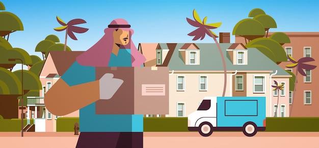 Mannelijke arabische koerier in masker en handschoenen met kartonnen doos contactloze levering medische koerier dienstverleningsconcept horizontale portret vectorillustratie