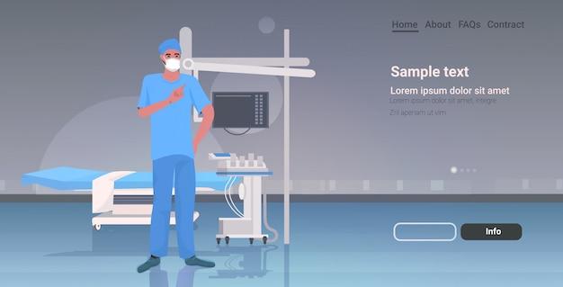 Mannelijke arts chirurg in beschermend masker en handschoenen ziekenhuis medische kliniek werknemer in uniforme geneeskunde gezondheidszorg concept moderne kliniek chirurgie kamer interieur volledige lengte kopie ruimte horizontaal