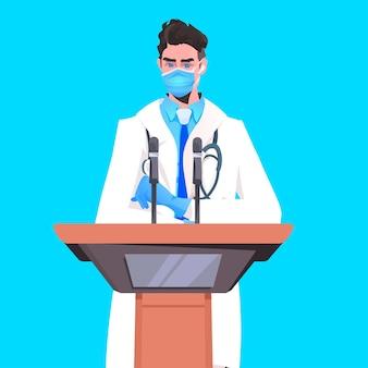 Mannelijke arts in masker houdt toespraak op tribune met microfoon strijd tegen coronavirus medische conferentie
