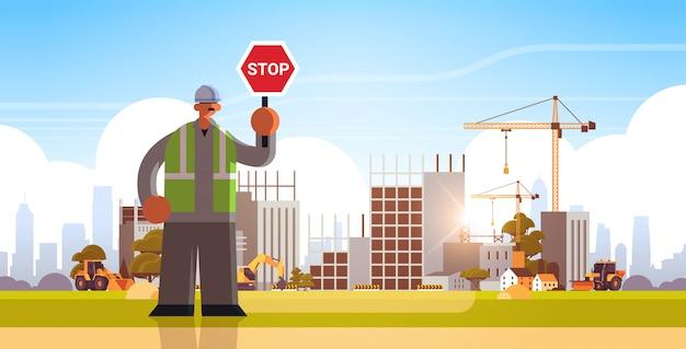 Mannelijke bouwer holding stop teken sluiten of blokkeren manier werkman permanent pose industriële arbeider in uniform gebouw concept bouwplaats achtergrond plat volledige lengte horizontaal