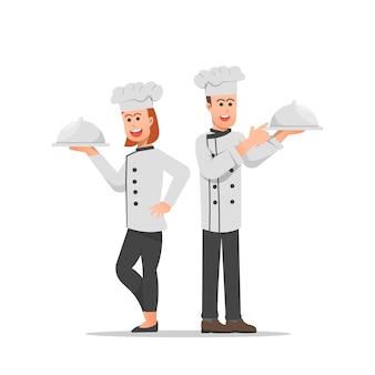 Mannelijke en vrouwelijke chef-koks poseren met overdekte gerechten