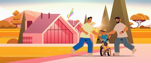 Mannelijke ouders leren zoontje fietsen homoseksuele familie transgender liefde lgbt-gemeenschapsconcept