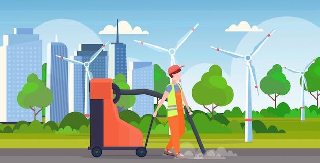 Mannelijke straat conciërge bedrijf industriële stofzuiger man stofzuigen vuilnis straten schoonmaak service concept moderne windturbines stadsgezicht achtergrond volledige lengte vlak en horizontaal