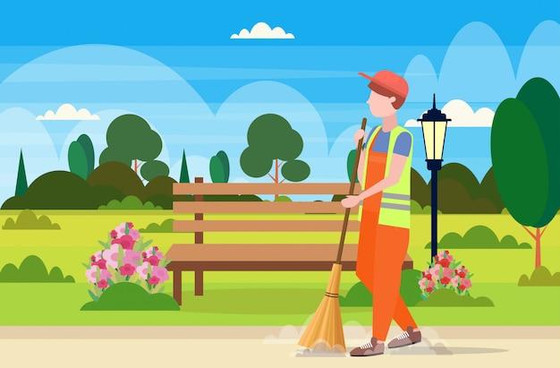 Mannelijke straat schonere bezem man vegen vuilnis schoonmaak concept stadspark landschap achtergrond volledige lengte vlak en horizontaal