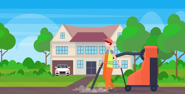 Mannelijke straat werknemer met industriële stofzuiger man stofzuigen vuilnis straten schoonmaak concept moderne cottage huis platteland achtergrond volledige lengte vlak en horizontaal