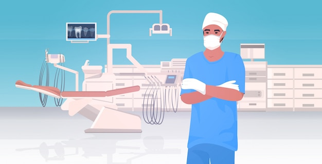 Mannelijke tandarts in beschermend masker en handschoenen gevouwen handen ziekenhuis medische kliniek werknemer in uniform geneeskunde gezondheidszorg concept moderne tandheelkundige kliniek interieur portret horizontaal