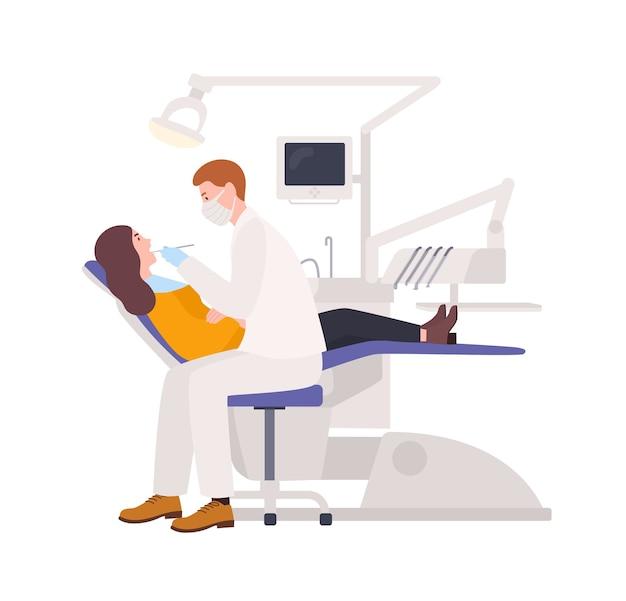 Mannelijke tandartsen die vrouwelijke patiënt onderzoeken die in stoel liggen. kaakchirurg die geïsoleerde vrouw behandelt. medisch onderzoek in mondverzorgingskliniek