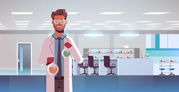 Mannelijke wetenschapper die reageerbuizen met kleurrijke vloeistof houdt