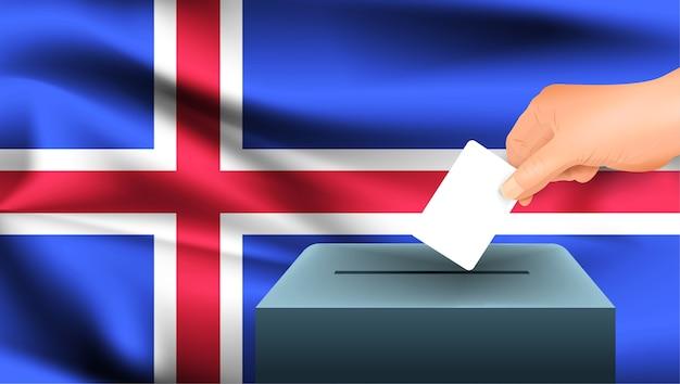 Mannenhand legt een wit vel papier met een merkteken neer als symbool van een stembiljet tegen de achtergrond van de ijslandse vlag. ijsland het symbool van verkiezingen