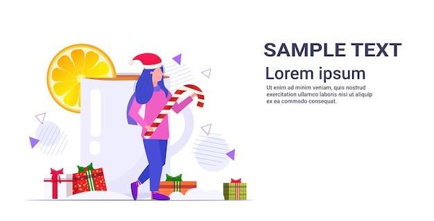 Meisje bedrijf candy cane lollipop staande in de buurt van kerst drankje glühwein wintervakantie viering