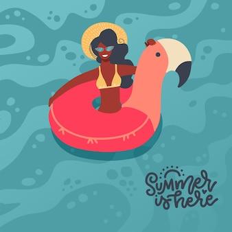 Meisje dat op de roze cirkel van de flamingovlotter zwemt