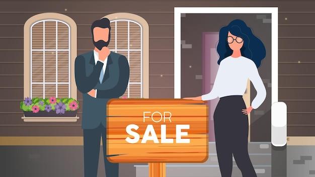 Meisje en de man zijn makelaars. makelaars met een te koop-teken. concept van de verkoop van appartementen, huizen en onroerend goed. vector.