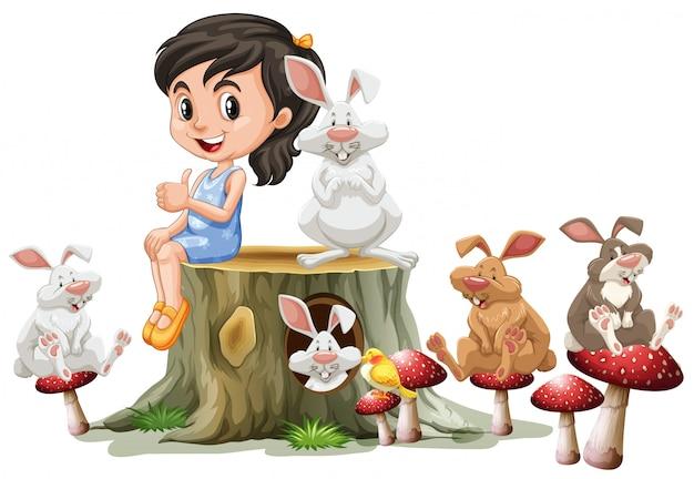 Meisje en schattige konijnen op logboek