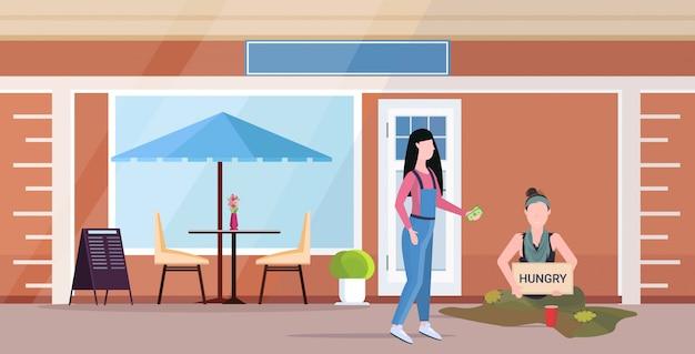 Meisje geld geven aan trieste vrouw bedelaar bedrijf bord met hongerige tekst meisje vagebond bedelen voor hulp daklozen concept café gebouw buitenkant plat volledige lengte horizontaal