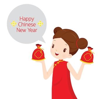 Meisje in cheongsam met geldzakken, traditionele viering, china, gelukkig chinees nieuwjaar
