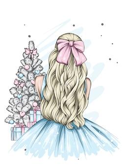 Meisje in een mooie jurk in de buurt van de kerstboom.