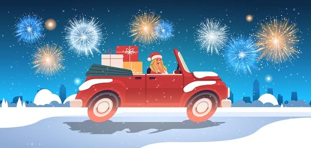 Meisje in het kostuum van de kerstman die geschenken op rode auto levert vrolijk kerstfeest gelukkig nieuwjaar vakantie viering concept vuurwerk in nacht hemel stadsgezicht achtergrond horizontale vectorillustratie