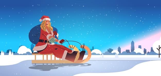 Meisje in kerstman kostuum rijden slee gelukkig nieuwjaar vrolijk kerstfeest vakantie viering concept winter stadsgezicht achtergrond horizontale volledige lengte vectorillustratie