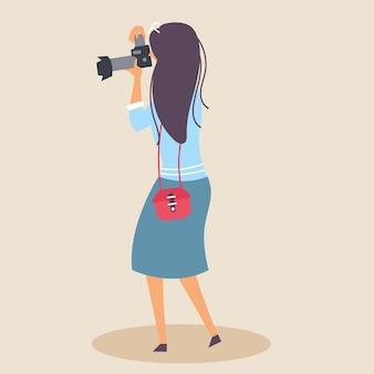 Meisje met een handtas maakt een foto met een spiegelreflexcamera in een natuurlijke omgeving