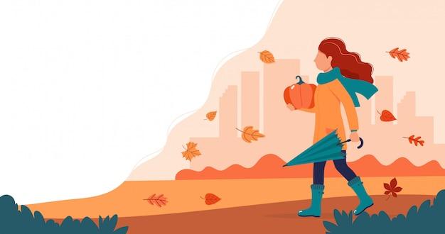 Meisje met een pompoen in de herfst.