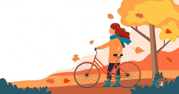 Meisje met fiets in het park in de herfst.