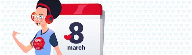 Meisje over kalenderpagina met 8 maart-datumachtergrond met het concept van de de dagvakantie van copyspace gelukkige vrouwen