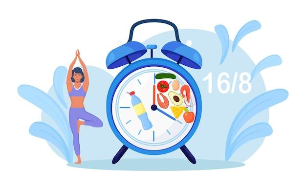 Meisje staat gebalanceerd in boomhouding en wacht op tijd om te eten. yoga. geduld. intermitterend vasten. vrouw aan het sporten, fitness. dieet, goede voeding. tijd beperkt eten. voedselinname klok