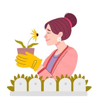 Meisje tuinman met een gele bloem in haar handen.
