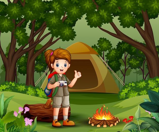 Meisjesontdekkingsreiziger met verkenner het eenvormige kamperen in het bos