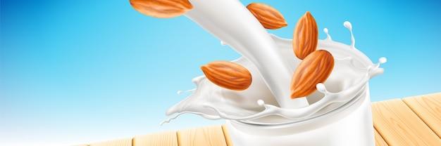 Melk splash met vloeistof naar beneden gieten in glazen beker met vliegende amandelpitten geïsoleerd