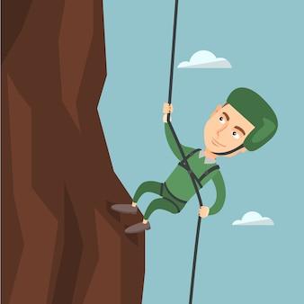 Mens die een berg met een kabel beklimt.