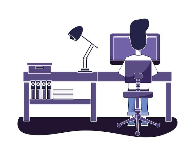 Mens die in a werkt een bureau met computer en lamp