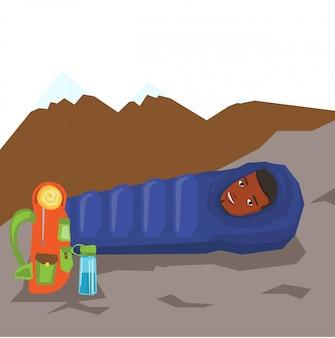 Mens die in slaapzak in de bergen rust.