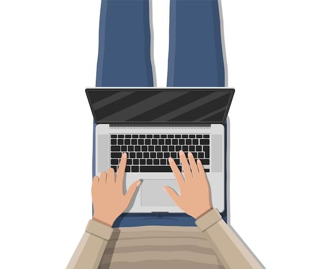 Mens die op banklaag ligt en laptop met behulp van