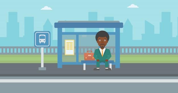 Mens die op bus bij de bushalte wacht.