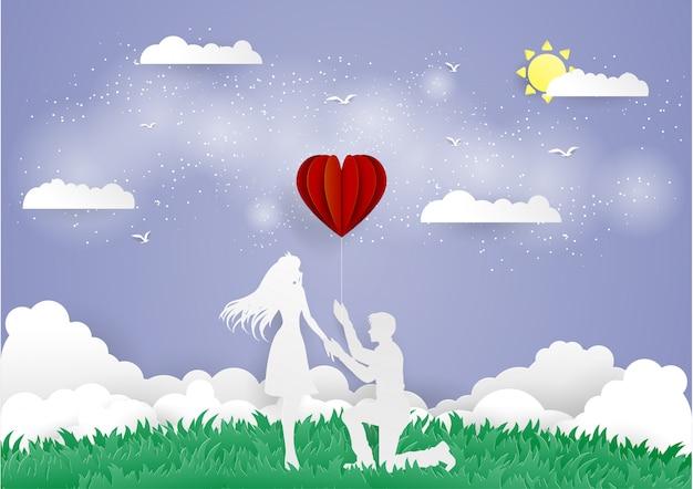 Mens die op de knie blijft en rode hartballon ganim
