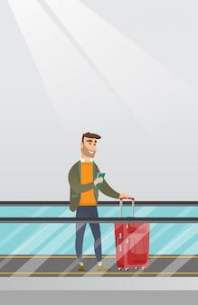 Mens die smartphone op roltrap gebruiken bij de luchthaven.