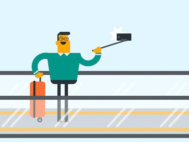Mens die smartphone op roltrap gebruiken bij de luchthaven