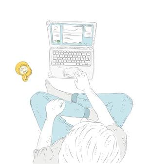 Mens met laptop thuis, zittend op de vloer.