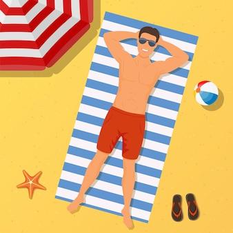 Mens op het strand. zomer tijd. man draagt liggend op het strand op een wit en blauw gestreepte handdoek