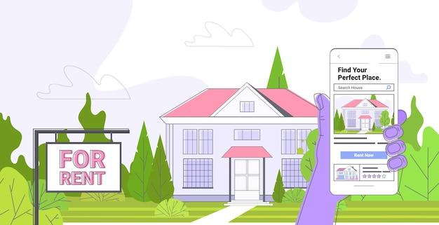 Menselijke hand met behulp van mobiele app voor het zoeken naar huizen voor het huren of kopen van online vastgoedbeheerconcept horizontaal